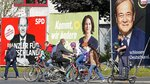People walk and drive past election posters of the three chancellor candidates, from right, Armin Laschet, Christian Democratic Union (CDU), Annalena Baerbock, German Green party (Die Gruenen) and Olaf Scholz, Social Democratic Party (SPD), at a street in Gelsenkirchen, Germany, Thursday, Sept. 23, 2021 three days before the General election on Sunday, Sept. 26, 2021. (AP Photo/Martin Meissner)
