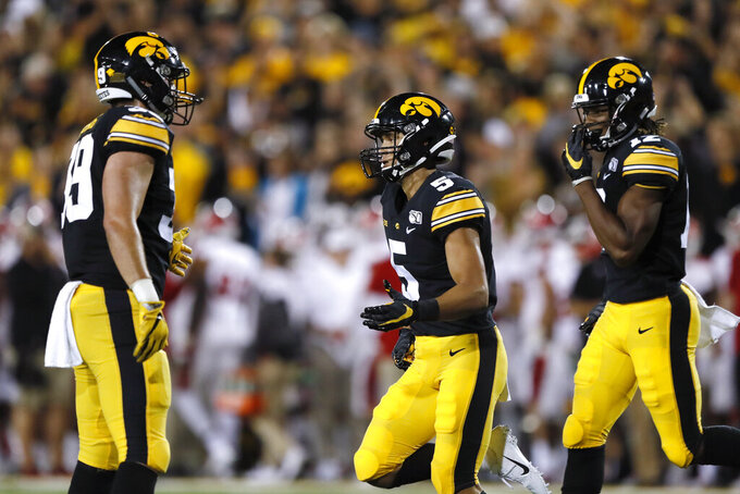 Iowa wide receiver Oliver Martin, center, celebrates with teammates Nate Wieting, left, and Brandon Smith, right, after catching a touchdown pass during the second half of an NCAA college football game against Miami of Ohio, Saturday, Aug. 31, 2019, in Iowa City, Iowa. Iowa won 38-14. (AP Photo/Charlie Neibergall)