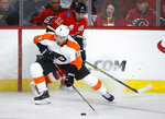 Philadelphia Flyers' Ivan Provorov, front, steals the puck from Calgary Flames' Mikael Backlund during the second period of an NHL hockey game Tuesday, Oct. 15, 2019, in Calgary, Alberta. (Jeff McIntosh/The Canadian Press via AP)