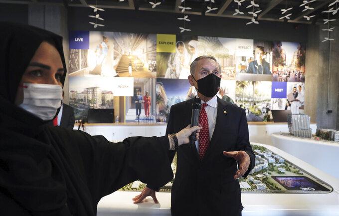 U.S. Ambassador John Rakolta talks with a UAE TV presenter during the U.S.A Pavilion handover ceremony at the Dubai Expo 2020, United Arab Emirates, Wednesday, Nov. 18, 2020. The U.S. showed off a literally star-studded pavilion Wednesday for Dubai's upcoming Expo 2020, complete with a replica SpaceX rocket body beside it. (AP Photo/Kamran Jebreili)