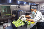 Hanan Shabazz cuts broccoli to prep it for a soup at the Southside Kitchen in Asheville, N.C., Wednesday, Oct. 14, 2020. The staff was feeding about 500 people that day she said. The Southern Foodways Alliance has awarded Shabazz its annual Ruth Fertel Keeper of the Flame Award for her culinary and community work. (Angeli Wright/The Asheville Citizen-Times via AP)