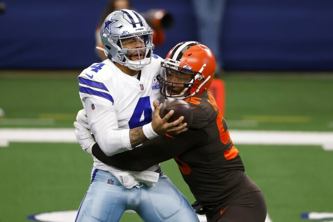 Dallas Cowboys quarterback Dak Prescott (4) is sacked by Cleveland Browns defensive end Myles Garrett (95) in the first half of an NFL football game in Arlington, Texas, Sunday, Oct. 4, 2020. (AP Photo/Ron Jenkins)