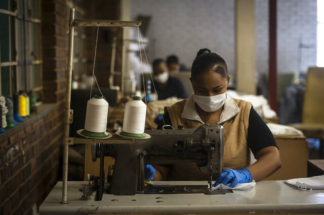 A woman sews face masks at a furniture factory in Eldorado Park, Johannesburg, Tuesday, March 24, 2020, in their fight against the coronavirus the day after it was announced that South Africa will go into a nationwide lockdown for 21 days from Thursday. For most people the virus causes only mild or moderate symptoms . For others it can cause more severe illness, especially in older adults and people with existing health problems. (AP Photo/Shiraaz Mohamed)