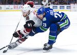 Arizona Coyotes left wing Taylor Hall (91) fights for control of the puck with Vancouver Canucks defenseman Alexander Edler (23) during the third period of an NHL hockey game Thursday, Jan. 16, 2020, in Vancouver, British Columbia. (Jonathan Hayward/The Canadian Press via AP)