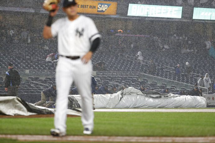 Grounds crew workers roll out the tarp during the seventh inning of a baseball game between the Chicago White Sox and the New York Yankees, Friday, April 12, 2019, in New York. (AP Photo/Michael Owens)