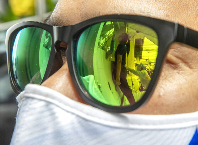 Health workers collecting a nasal swab from a woman are reflected on the sunglasses in Rayong province, Thailand, Tuesday, July 14, 2020. Authorities set up testing for anyone concerned they might have come into contact with an Egyptian soldier who visited a shopping mall in Rayong last week and then tested positive for COVID-19. In Thailand, where there has been no reports of locally transmitted cases for seven weeks, health authorities were rushing to trace the contacts of two recent foreign arrivals in the country who were infected with the coronavirus and may have violated quarantine rules.(AP Photo/Sakchai Lalit)