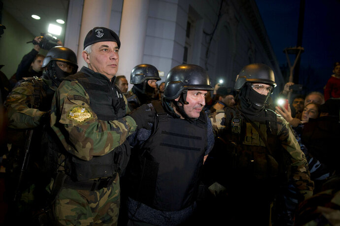 FILE - In this June 14, 2016 file photo, former Public Works Secretary Jose Lopez, center, is escort by police outside the a police station in the outskirts of Buenos Aires, Argentina. A court in Argentina sentenced Lopez on Wednesday, June 12, 2019, to 6 years in prison for illicit enrichment after he tried to hide millions of dollars in cash at a convent. (AP Photo/Natacha Pisarenko, File)