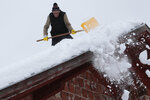 A man shovels snow from the roof of his house in a remote village near Kladanj, 80 kms north of Sarajevo, Bosnia, Friday, Jan. 11, 2019. Heavy snow descended on Balkan countries causing havoc in traffic and state or emergency declared in some areas.(AP Photo/Amel Emric)