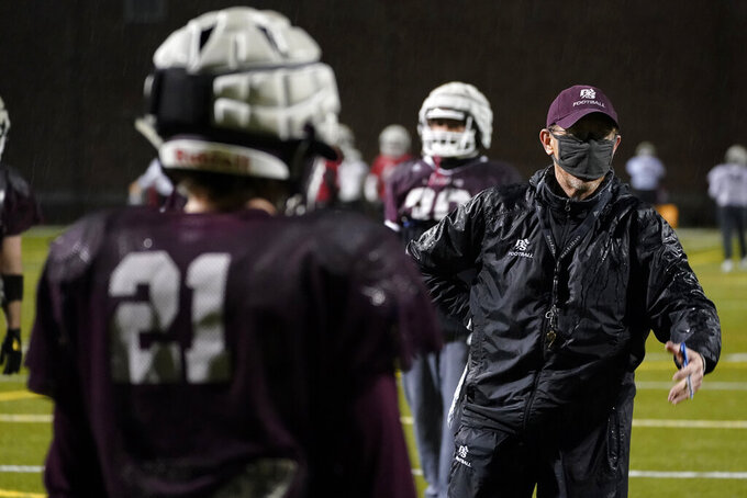 Jeff Housman, right, defensive coordinator at the University of Puget Sound, wears a mask as he talks with players during college football practice Tuesday, Feb. 2, 2021, in Tacoma, Wash. For all the attention heaped on the FBS level of college football last fall as it tried to play, it will not be the only college football during the 2020-21 sports calendar as a handful of NCAA Division III and NAIA programs begin some form of a winter/spring season Saturday, Feb. 6. (AP Photo/Ted S. Warren)