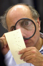 "FILE - In this Nov. 24, 2000 file photo, Broward County canvassing board member Judge Robert Rosenberg uses a magnifying glass to examine a disputed ballot at the Broward County Courthouse in Fort Lauderdale, Fla. The Florida recount, with its hanging chads and razor-thin margins, may seem like a long time ago. But a new HBO documentary, produced by Adam McKay, titled ""537 Votes"" delves into recent history to remind voters this November about how much their ballots can matter. (AP Photo/Alan Diaz, File)"