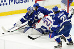 Tampa Bay Lightning goaltender Andrei Vasilevskiy, Lightning center Brayden Point (21) and Montreal Canadiens center Eric Staal (21) reach for the puck during the first period in Game 5 of the NHL hockey Stanley Cup finals, Wednesday, July 7, 2021, in Tampa, Fla. (AP Photo/Gerry Broome)