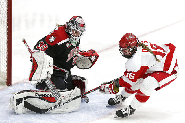 In this Feb. 2, 2016, photo, Northeastern goalie Brittany Bugalski (39) makes the save on a shot by Boston University forward Sammy Davis (16) during the first period of a women's Beanpot NCAA college hockey match in Boston. The Boston Pride selected Boston University forward Sammy Davis with the first pick in the NWHL Draft on Tuesday night, April 28, 2020. (Barry Chin/The Boston Globe via AP)