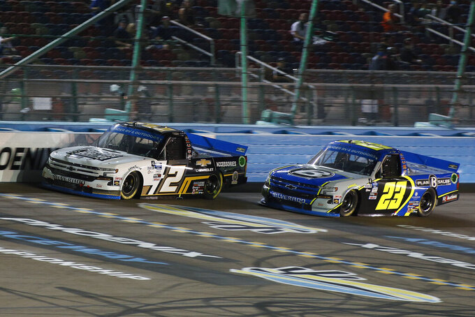 Sheldon Creed (2) and Brett Moffitt (23) race for the lead during the NASCAR Truck Series auto race at Phoenix Raceway, Friday, Nov. 6, 2020, in Avondale, Ariz. (AP Photo/Ralph Freso)