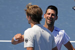 Novak Djokovic, of Serbia, right, talks with Alexander Zverev, of Germany after their practice for the men's tennis competition at the 2020 Summer Olympics, Thursday, July 22, 2021, in Tokyo. (AP Photo/Charlie Riedel)