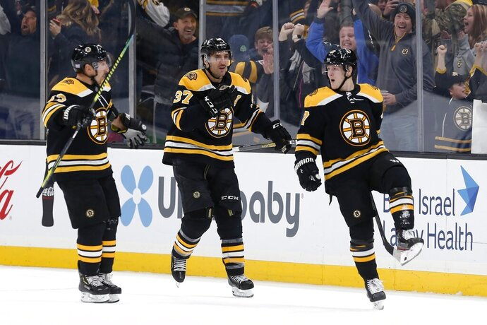 Boston Bruins' Torey Krug (47) celebrates his game-winning goal with Patrice Bergeron (37) and Brad Marchand (63) in overtime during an NHL hockey game in Boston, Saturday, Nov. 23, 2019. (AP Photo/Michael Dwyer)