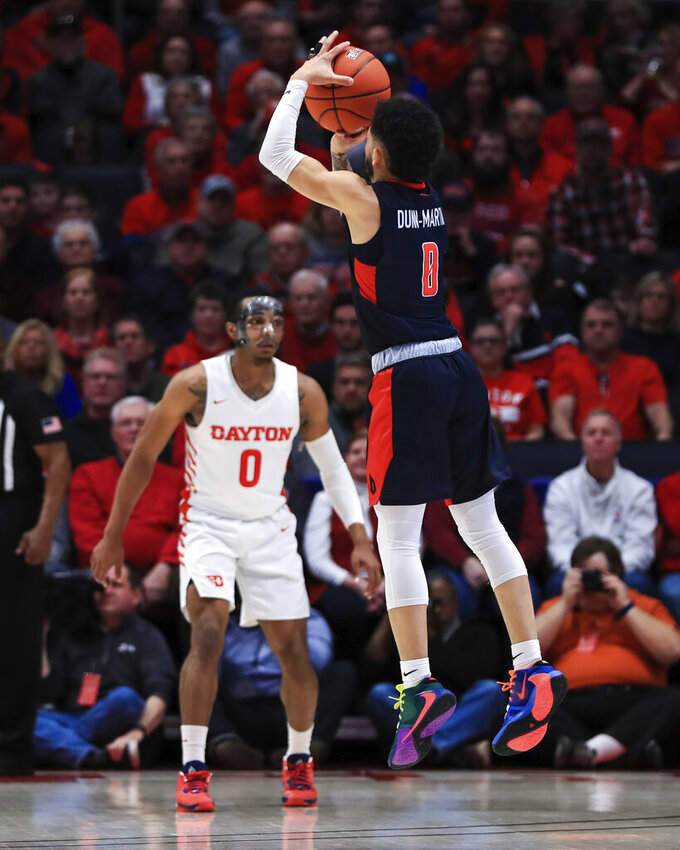 Duquesne's Tavian Dunn-Martin (0) makes a 3-point basket in the first half of an NCAA college basketball game against Dayton, Saturday, Feb. 22, 2020, in Dayton, Ohio. (AP Photo/Aaron Doster)