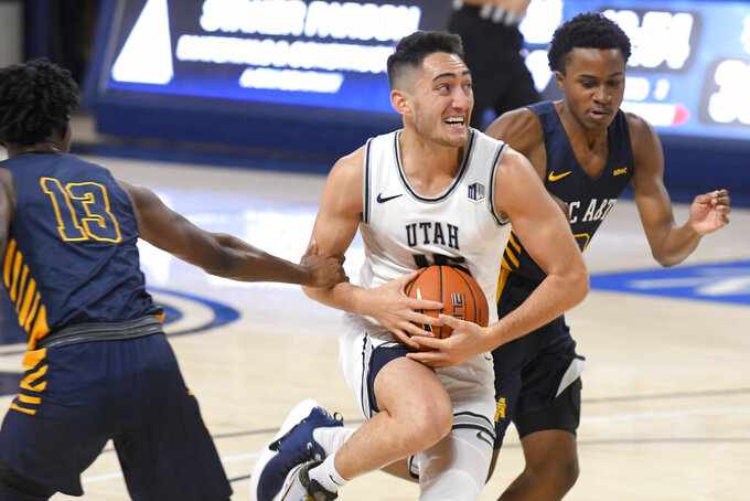 Utah State guard Abel Porter, center, is fouled by North Carolina A&T guard Kameron Langley (13) as guard Fred Cleveland Jr. helps defend during the second half of an NCAA college basketball game Friday, Nov. 15, 2019, in Logan, Utah. (AP Photo/Eli Lucero)