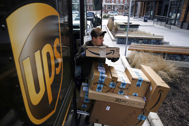 FILE- In this Dec. 19, 2018, file photo a UPS driver prepares to deliver packages. UPS says it plans to hire more than 100,000 extra workers to help handle an increase in packages during the holiday season. UPS said Wednesday, Sept. 9, 2020, that it expects a record peak season. (AP Photo/Patrick Semansky, File)
