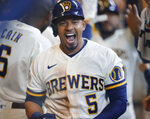 Milwaukee Brewers' Eduardo Escobar celebrates in the dugout after his three-run home run against the Pittsburgh Pirates during the seventh inning of a baseball game Monday, Aug. 2, 2021, in Milwaukee. (AP Photo/Jeffrey Phelps)