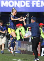 Sweden's Sofia Jakobsson, left, jumps as she celebrates with Sweden coach Peter Gerhardsson after scoring her side's first goal during the of the Women's World Cup quarterfinal soccer match between Germany and Sweden at Roazhon Park in Rennes, France, Saturday, June 29, 2019. (AP Photo/David Vincent)