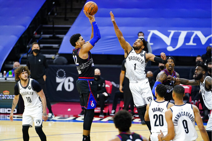 Philadelphia 76ers' Tobias Harris (12) goes up for a shot against Brooklyn Nets' Bruce Brown (1) during the second half of an NBA basketball game, Saturday, Feb. 6, 2021, in Philadelphia. (AP Photo/Matt Slocum)