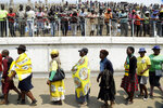 Zimbabweans queue to pay their last respects at the coffin of former Zimbabwean President Robert Mugabe at the Rufaro Stadium in Harare, Friday, Sept. 13, 2019, where the body is on view at the stadium for a second day. Mugabe died last week in Singapore at the age of 95. He led the southern African nation for 37 years before being forced to resign in late 2017. (AP Photo/Themba Hadebe)