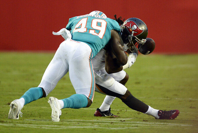 Miami Dolphins linebacker Sam Eguavoen (49) knocks the ball away from Tampa Bay Buccaneers running back Andre Ellington for a fumble during the first half of an NFL preseason football game Friday, Aug. 16, 2019, in Tampa, Fla. Miami recovered the ball. (AP Photo/Jason Behnken)