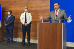 """FILE - In this April 21, 2021 file photo, Columbus Mayor Andrew Ginther, right, speaks during a news conference in Columbus, Ohio. The announcement that the U.S. Justice Department will provide technical assistance to Columbus police — at the city's invitation — has done little to curb community activists' allegations that officials aren't doing enough to change the department following a series of fatal police shootings of Black people. On Thursday, Sept. 16, 2021 the activists asked the Justice Department to launch an investigation through its Civil Rights Division, a probe sometimes called a """"pattern-or-practice"""" investigation that can lead to court-ordered oversight of a troubled police department. (AP Photo/Andrew Welsh-Huggins, File)"""
