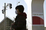 A woman wearing a protective mask to help curb the spread of the coronavirus walks near one of the Olympic venues in Tokyo Wednesday, Jan. 20, 2021. The Japanese capital confirmed more than 1,200 new coronavirus cases on Wednesday. (AP Photo/Eugene Hoshiko)