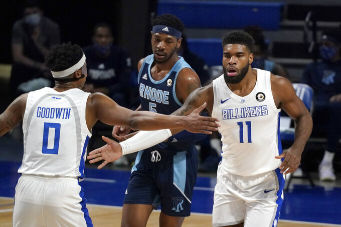 Saint Louis' Hasahn French (11) is congratulated by teammate Jordan Goodwin (0) after making a layup as Rhode Island's Antwan Walker watches during the first half of an NCAA college basketball game Wednesday, Feb. 10, 2021, in St. Louis. (AP Photo/Jeff Roberson)