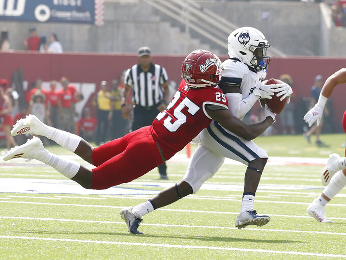 Connecticut wide receiver Cameron Ross, right, runs past Fresno State defensive back Emari Pait (25) during the first half of an NCAA college football game in Fresno, Calif., Saturday, Aug. 28, 2021. (AP Photo/Gary Kazanjian)