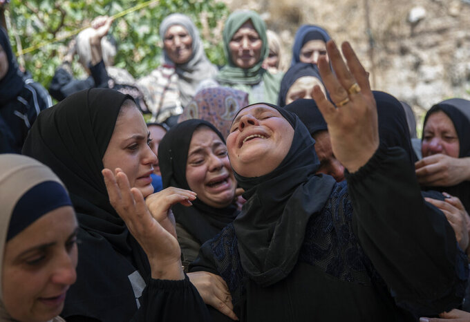 Palestinian mourners cry while taking the farewell look at the body Shaukat Awad, 20 during his funeral in the West Bank village of Beit Ummar, near Hebron, Friday, July. 30, 2021. Israeli troops shot and killed the 20 year old Palestinian man, Palestinian health officials said, during clashes that erupted in the occupied West Bank following the funeral of a Palestinian boy killed by army fire the previous day. (AP Photo/Nasser Nasser)