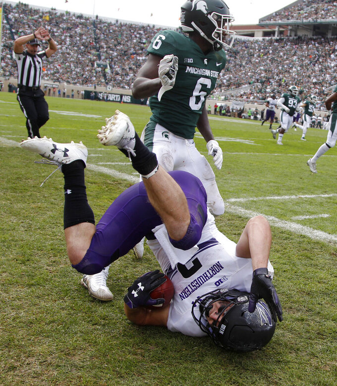 Northwestern's Flynn Nagel, bottom, tumbles after being forced out of bounds by Michigan State's David Dowell (6) in the third quarter of an NCAA college football game, Saturday, Oct. 6, 2018, in East Lansing, Mich. Northwestern won 29-19. (AP Photo/Al Goldis)
