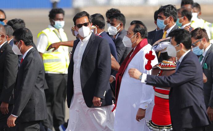 Pakistan's Prime Minister Imran Khan, center, walks with Sri Lankan Prime Minister Mahinda Rajapaksa upon his arrival in Colombo, Sri Lanka, Tuesday, Feb. 23, 2021. Khan is in Sri Lanka for a two day official visit. (AP Photo/Eranga Jayawardena)