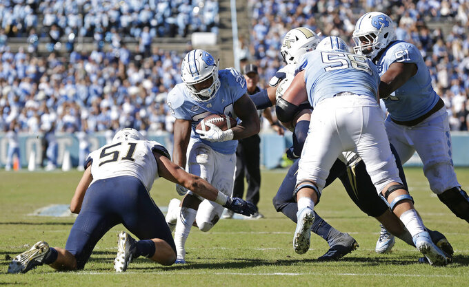 North Carolina's Antonio Williams (24) runs the ball while Georgia Tech's Brant Mitchell (51) reaches in to tackle during the first half of an NCAA college football game in Chapel Hill, N.C., Saturday, Nov. 3, 2018. (AP Photo/Gerry Broome)