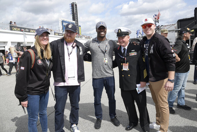 Driver Jesse Iwuji, center, poses with military personnel and staff from Barstool Sports, including Barstool personality Uncle Chaps, second from left, during a practice session for the NASCAR Daytona 500 auto race at Daytona International Speedway Saturday, Feb. 16, 2019, in Daytona Beach, Fla. (AP Photo/Phelan M. Ebenhack)