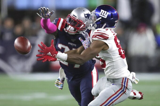 New England Patriots defensive back J.C. Jackson, left, breaks up a pass intended for New York Giants wide receiver Darius Slayton in the second half of an NFL football game, Thursday, Oct. 10, 2019, in Foxborough, Mass. (AP Photo/Charles Krupa)