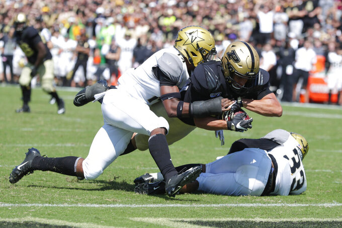 Purdue tight end Brycen Hopkins (89) dives in for a touchdown as he's hit by Vanderbilt safety Max Worship (14) and safety Dashaun Jerkins (33) during the second half of an NCAA college football game in West Lafayette, Ind., Saturday, Sept. 7, 2019. Purdue defeated Vanderbilt 42-24. (AP Photo/Michael Conroy)