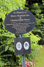 A makeshift memorial stands next to a new Mississippi historical marker that was dedicated Thursday, July 15, 2021, in Meadville, Miss., to remember Charles Eddie Moore and Henry Hezekiah Dee, who were kidnapped and killed by Ku Klux Klansmen in 1964. Law enforcement officers found the remains of the two Black teenagers in the Mississippi River while searching for three civil rights workers who had been kidnapped and killed by the Klan in June 1964 in a different part of Mississippi. A reputed Klansman, James Ford Seale, was convicted in 2007 in federal court in Jackson, Miss., on charges of kidnapping and conspiracy related to the fatal abduction of Dee and Moore. Seale died in prison in 2011. (AP Photo/Emily Wagster Pettus)