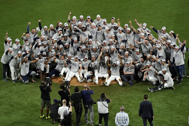 Tampa Bay Rays pose with the American League championship trophy following their victory against the Houston Astros in Game 7 of a baseball American League Championship Series, Saturday, Oct. 17, 2020, in San Diego. The Rays defeated the Astros 4-2 to win the series 4-3 games. (AP Photo/Jae C. Hong)