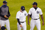 FILE - In this Tuesday, Sept. 1, 2020, file photo, New York Yankees manager Aaron Boone, left, keeps watch on New York Yankees relief pitcher Aroldis Chapman as a teammate escorts Chapman off the field after benches cleared following a pitch Chapman threw close to Tampa Bay Rays pinch hitter Michael Brosseau's head during the ninth inning of a baseball game at Yankee Stadium in New York. The Rays wear blue T-shirts with four horses lined up behind a fence, a reference to Tampa Bay manager Kevin Cash declaring