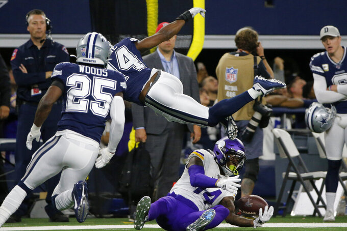 Dallas Cowboys free safety Xavier Woods (25) watches as Chidobe Awuzie (24) leaps over Dallas Cowboys wide receiver Lance Lenoir (14), who catches a pass while on the ground during the first half of an NFL football game in Arlington, Texas, Sunday, Nov. 10, 2019. (AP Photo/Michael Ainsworth)