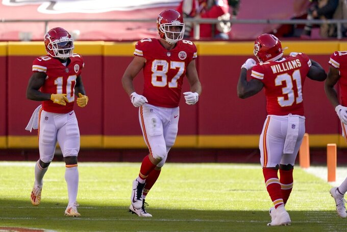 Kansas City Chiefs' Tyreek Hill (10), Travis Kelce (87) and Darrel Williams (31) celebrate a touchdown catch made by Kelce in the first half of an NFL football game against the New York Jets on Sunday, Nov. 1, 2020, in Kansas City, Mo. (AP Photo/Charlie Riedel)