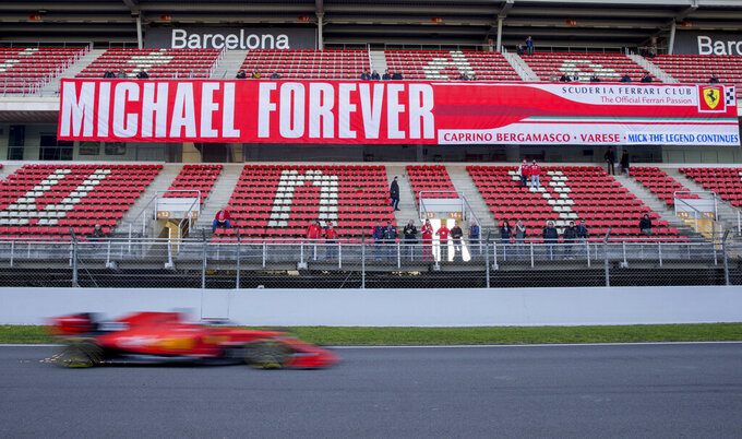 Ferrari driver Charles Leclerc of Monaco drives past a banner in support of former Ferrari driver Michael Schumacher during a Formula One pre-season testing session at the Barcelona Catalunya racetrack in Montmelo, outside Barcelona, Spain, Thursday, Feb. 28, 2019. (AP Photo/Joan Monfort)