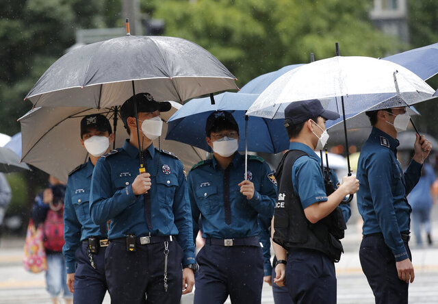 Police officers wearing face masks to help protect against the spread of the coronavirus, walk in downtown Seoul, South Korea, Monday, Sept. 7, 2020. (AP Photo/Lee Jin-man)