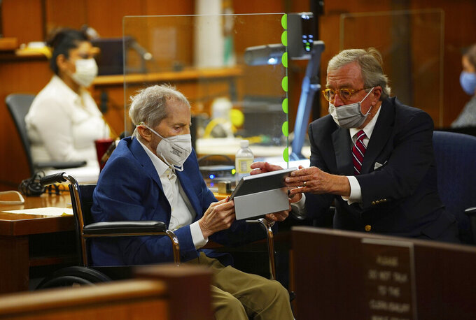 Defense attorney Dick DeGuerin, right, gives Robert Durst a device to read the real time spoken script as he appears in a courtroom as Judge Mark E. Windham gives last instructions to jurors before attorneys begin opening statements at the Los Angeles County Superior Court, Tuesday, May 18, 2021, in Inglewood, Calif. Durst, 78, is charged with one count of murder — in the killing of his best friend, Susan Berman, in 2000 in her Los Angeles home. (Al Seib/Los Angeles Times via AP, Pool)