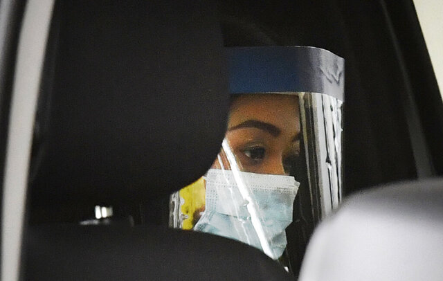 Sarah Caisip wears a protective mask after viewing her father's body at a funeral home in Brisbane, Thursday, Sept. 10, 2020. Caisip was refused permission to go to her father Bernard Prendergast's funeral because she was forced to spend 14 days in a hotel quarantine. (Darren England/AAP Image via AP)