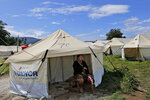 In this Monday, April 1, 2019, photo, a woman sits under a tent at a temporary shelter for those affected by Sept. 28, 2018, earthquake and liquefaction in Palu, Central Sulawesi, Indonesia. Six months after the city was ripped apart by an earthquake, tsunami and liquifying soil that sucked neighborhoods into the earth, thousands of people are living in sweltering tent cities and almost a third of temporary housing is unoccupied after aid groups and authorities failed to connect it to water or electricity. (AP Photo/Tatan Syuflana)