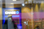 A customer is seen behind broken glass at a Chase ATM, Wednesday, Oct. 28, 2020, on Court Street in the Boerum Hill neighborhood of the Brooklyn borough of New York. Demonstrators protesting the police shooting of a Black man in Philadelphia broke store windows, set fires and vandalized police cars in Brooklyn Tuesday night, police said. (AP Photo/Mary Altaffer)