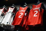 FILE - In this July 20, 2018, file photo, NBA jerseys for newly-acquired Toronto Raptors player Kawhi Leonard hang in the Real Sports Apparel store at Scotiabank Arena in Toronto. Companies that make clothing and shoes for the National Basketball Association players are in the crosshairs of President Donald Trump's escalating China trade wars. (Mark Blinch/The Canadian Press via AP, File)